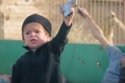 طفل داعشي يطلق النار على أحد السجناء